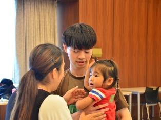 子どもを抱っこする心理学部相馬ゼミの学生